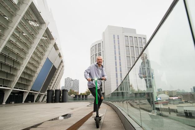 Leuke snelle rit op een elektrische scooter. jonge kerel in vrijetijdskleding huurde een e-scooter en heeft plezier. flatgebouwen op bakground. milieuvriendelijk transportconcept. stijlvolle man scooter rijden.