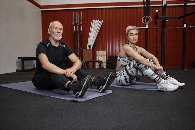 Leuke sportieve jonge vrouw met kort kapsel zittend op de vloer met aantrekkelijke bebaarde man gepensioneerde m / v in sportkleding met vermoeide gezichtsuitdrukkingen, ontspannen tussen sets van crossfit oefeningen