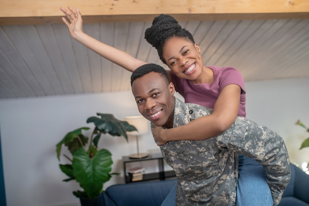 Leuke stemming. jonge afro-amerikaanse militaire man die zijn vrouw in een speelse bui thuis in een gezellige kamer gebarend naar achteren houdt