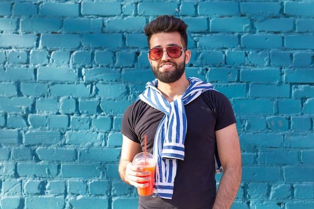 Leuke stijlvolle arabische jonge mannelijke hipster met een snor en een baard en een bril drinken van sap