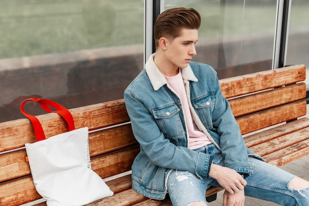 Leuke stijlvolle jongeman in trendy blauwe casual jeans voor jongeren, zittend op een houten bankje en wachtend op het openbaar vervoer. knappe jongen in stijlvolle kleding bij glazen bushalte. mode zomer herenkleding.