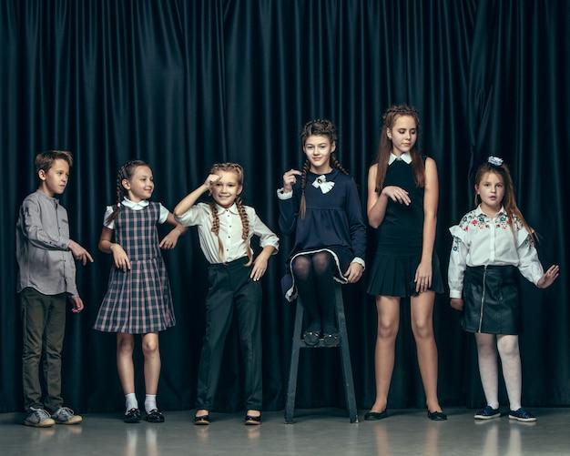 Leuke stijlvolle kinderen op donkere ruimte. de mooie tienermeisjes en de jongen die zich verenigen
