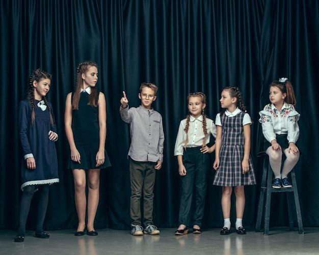 Leuke stijlvolle kinderen op donkere studio achtergrond. de mooie tienermeisjes en de jongen die zich verenigen