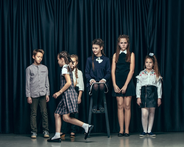 Leuke stijlvolle kinderen op donkere studio. de mooie tiener meisjes en jongen staan samen