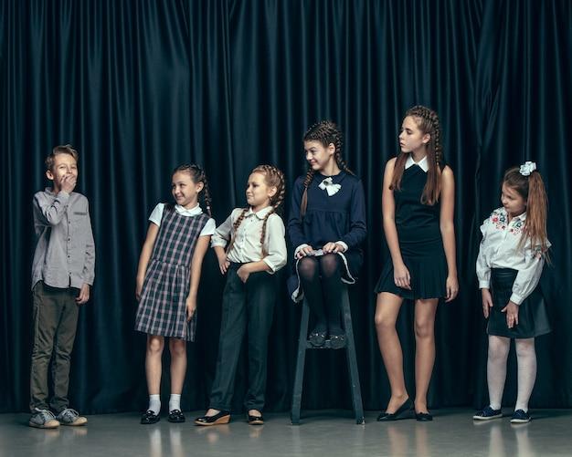 Leuke stijlvolle kinderen op donkere studio. de mooie tienermeisjes en de jongen die zich verenigen