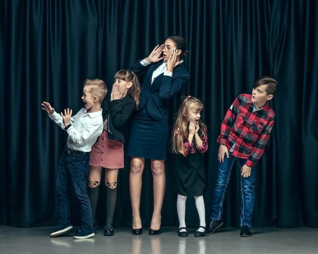 Leuke stijlvolle kinderen op donkere studio. mooie tienermeisjes en jongen die zich verenigen