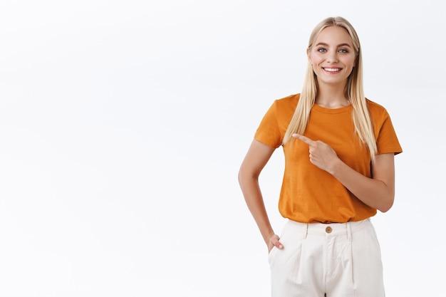 Leuke stijlvolle, moderne blonde vrouw die advies geeft, die een hangplek laat zien. aantrekkelijk kaukasisch meisje in oranje t-shirt, met de vinger naar links wijzend en vrolijk lachend, stel een koele plek voor, beveel link aan