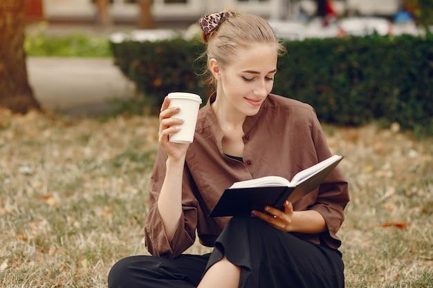 Leuke student die in een park werkt en het notitieboekje gebruikt