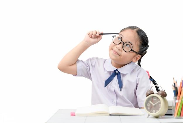 Leuke student die terwijl het doen van haar thuiswerk denkt