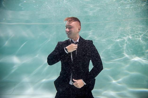 Leuke succesvolle jonge zakenman die zijn stropdas aanpast en naar onderwater kijkt. emotionele man persoon is directeur in vijver. concept van werkuren en het nemen van zakelijke beslissingen op kantoor. ruimte kopiëren