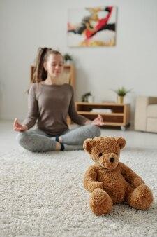 Leuke teddybeerzitting op tapijt met jonge actieve vrouw die meditatieoefening op achtergrond doen