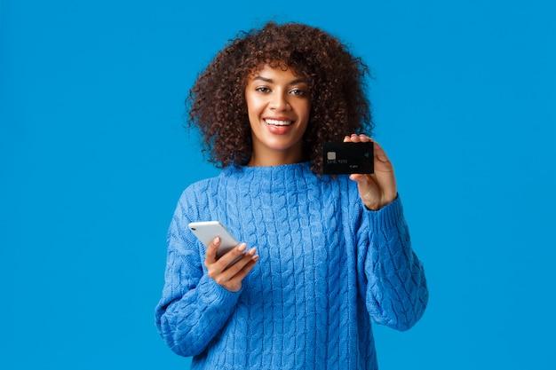 Leuke tevreden afro-amerikaanse vrouwelijke bankklant adviseert creditcard en banksysteem, houdt smartphone vast en glimlacht, koopt online, winkelt in internetwinkels, blauwe achtergrond