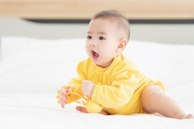 Leuke thaise pasgeboren baby grappig spelen in bed. kleine baby in luier liggend op zijn buik op wit bed met speelgoed