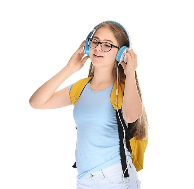 Leuke tiener die aan muziek op witte oppervlakte luistert
