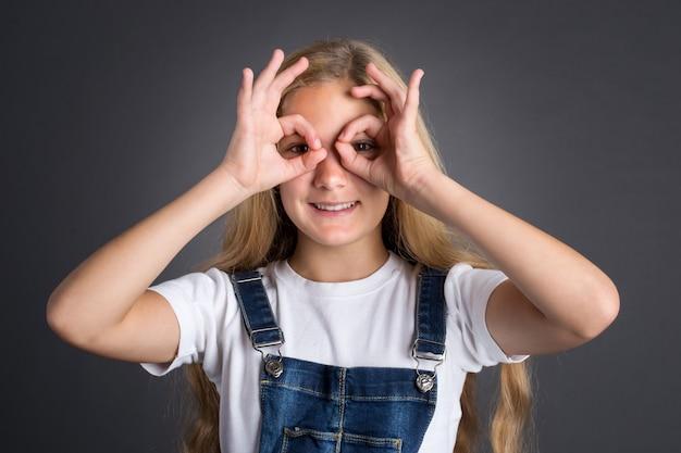 Leuke tiener die door denkbeeldige binoculair op grijze achtergrond kijkt.