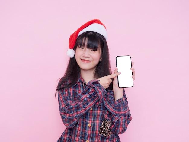 Leuke tiener die in kerstmanhoed smartphone met het lege scherm op roze muur houdt. ruimte voor tekst