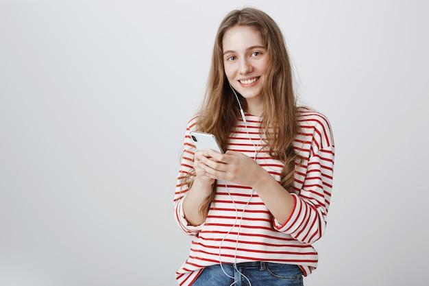 Leuke tiener die mobiele telefoon met behulp van en muziek in oortelefoons luisteren