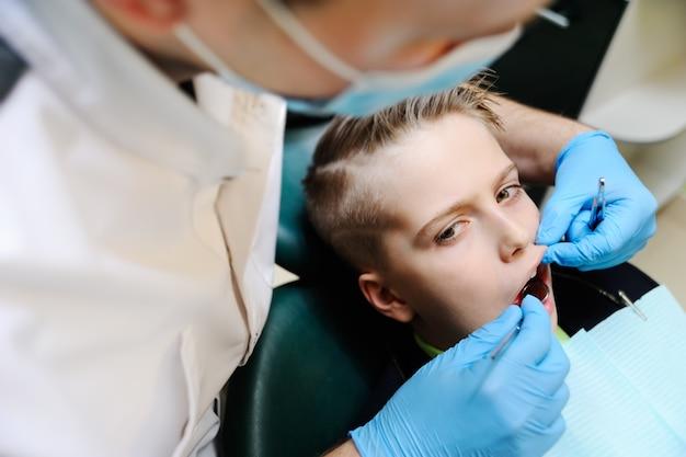 Leuke tiener - een jongen als tandvoorzitter op een onderzoek met een tandarts