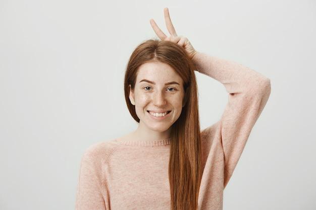 Leuke tiener met rood haar en sproeten die vredesteken tonen