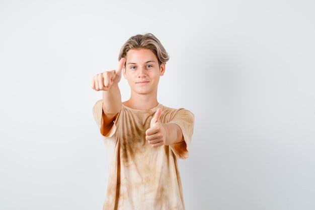 Leuke tienerjongen die dubbele duimen in t-shirt toont en er tevreden uitziet, vooraanzicht.