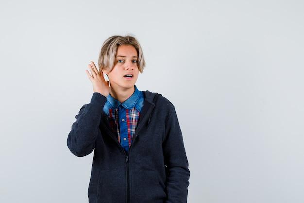 Leuke tienerjongen die hand achter het oor houdt in shirt, hoodie en nieuwsgierig kijkt. vooraanzicht.