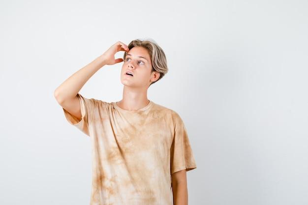 Leuke tienerjongen die hand op het hoofd houdt, omhoog kijkt in t-shirt en peinzend kijkt, vooraanzicht.