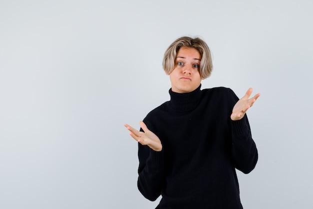 Leuke tienerjongen die hulpeloos gebaar toont in zwarte coltrui en er geen idee van heeft, vooraanzicht.