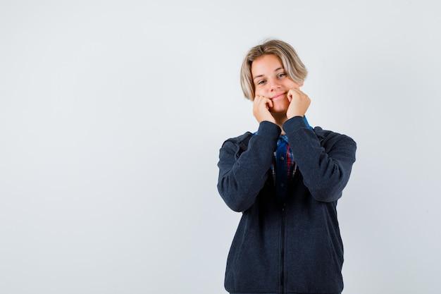 Leuke tienerjongen die wangen op handen in hoodie leunt en beschaamd kijkt. vooraanzicht.