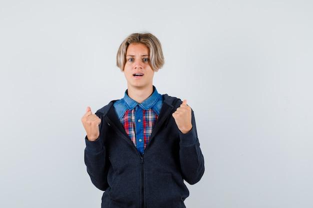 Leuke tienerjongen die winnaargebaar in overhemd, hoodie toont en gelukkig kijkt. vooraanzicht.