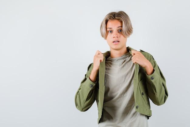 Leuke tienerjongen die zijn open jas in een groene jas trekt en er bang uitziet, vooraanzicht.