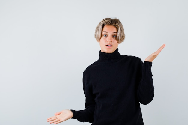 Leuke tienerjongen in coltrui die een hulpeloos gebaar toont en er verward uitziet