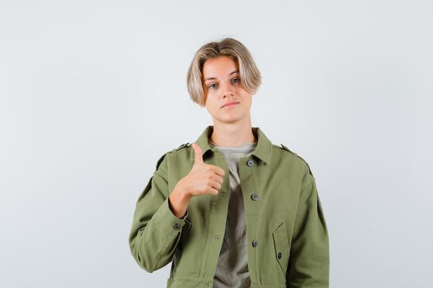 Leuke tienerjongen in een groene jas die duim toont en er zelfverzekerd uitziet, vooraanzicht.