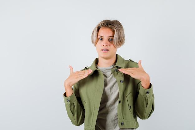Leuke tienerjongen in groene jas die naar zichzelf wijst en bang kijkt, vooraanzicht.