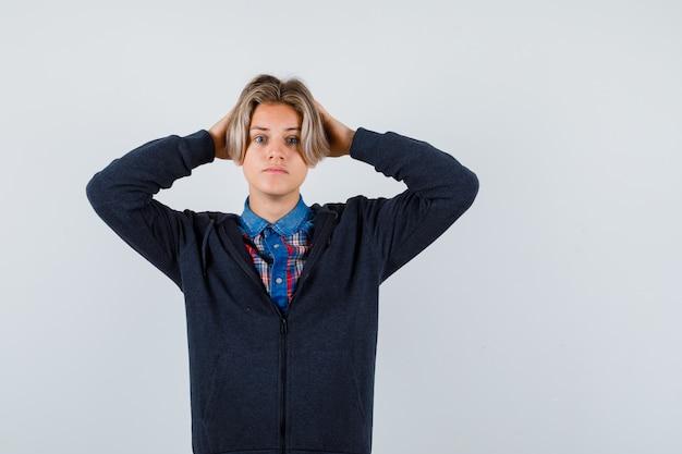 Leuke tienerjongen in overhemd, hoodie die handen op het hoofd houdt en angstig kijkt, vooraanzicht.