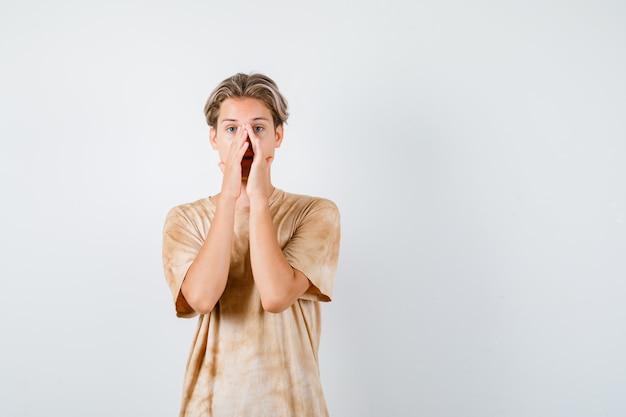 Leuke tienerjongen in t-shirt die de handen op de mond houdt en er bang uitziet, vooraanzicht.