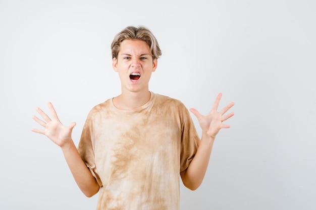 Leuke tienerjongen in t-shirt die overgavegebaar toont terwijl hij schreeuwt en doodsbang kijkt, vooraanzicht.