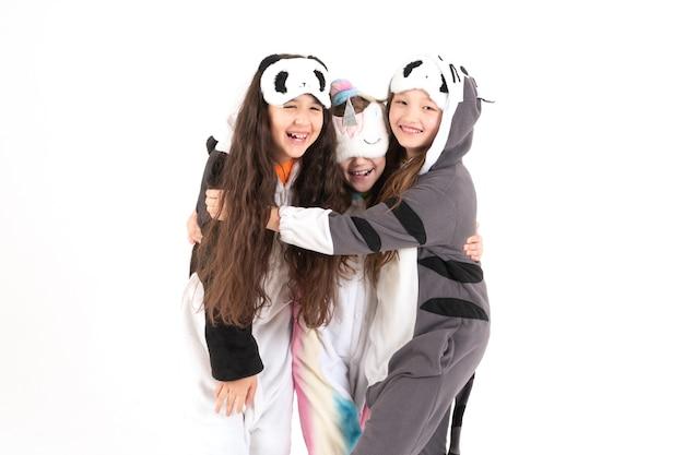 Leuke tienermeisjes in kigurumi en slaapmaskers glimlachen en knuffelen. wereldkinderen dag.