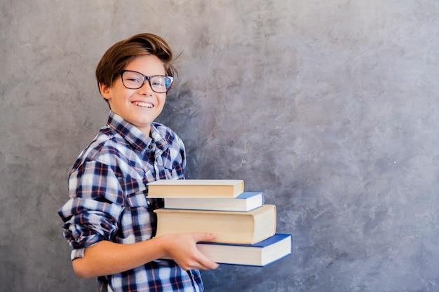 Leuke tienerschooljongen die boeken houdt