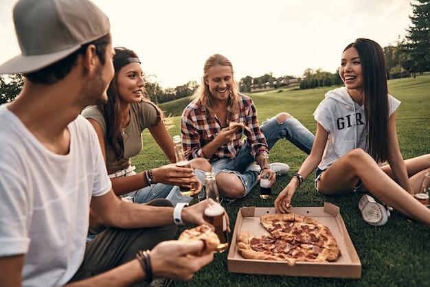 Leuke tijd met vrienden. groep jonge lachende mensen in vrijetijdskleding die genieten van pizza en bier terwijl ze buiten op het gras zitten