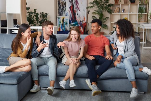 Leuke tijd samen doorbrengen met een groep jonge gelukkige multiculturele mensen in vrijetijdskleding die lacht terwijl