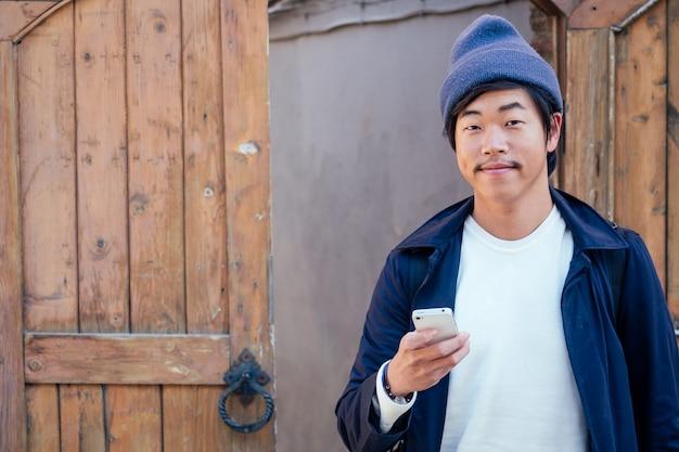 Leuke toerist uit korea met een rugzak die in de telefoon kijkt