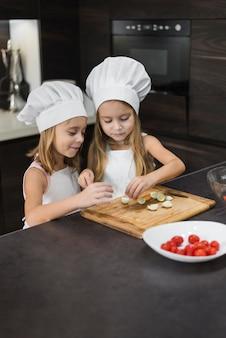 Leuke twee broers en zussen bereiden van voedsel in de keuken