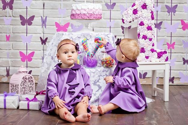 Leuke tweelingzusjes die hun 1ste verjaardag vieren