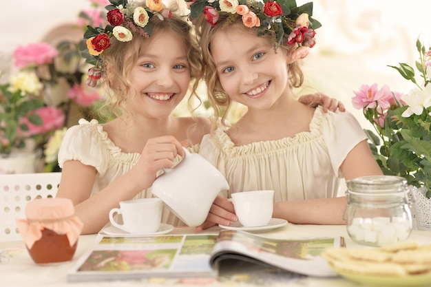 Leuke tweeniemeisjes in kransen met tijdschrift en thee thuis