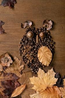 Leuke uilvorm van koffiebonen en kruiden. uil zit op de tak met koffiekopje en herfstbladeren over houten achtergrond. grappig mysterie koffie concept
