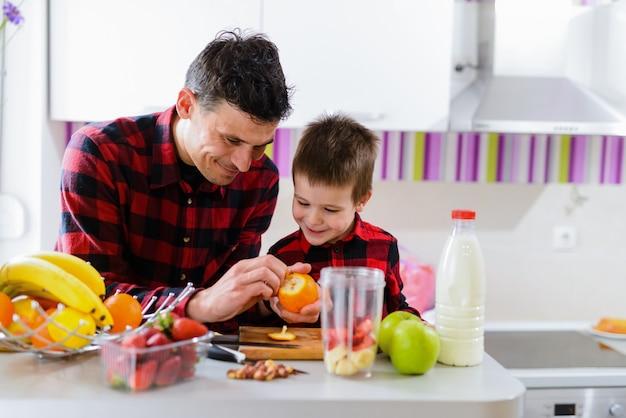 Leuke vader en zoon die samen gezond ontbijt maken. zittend aan de keukentafel vol met vers fruit.