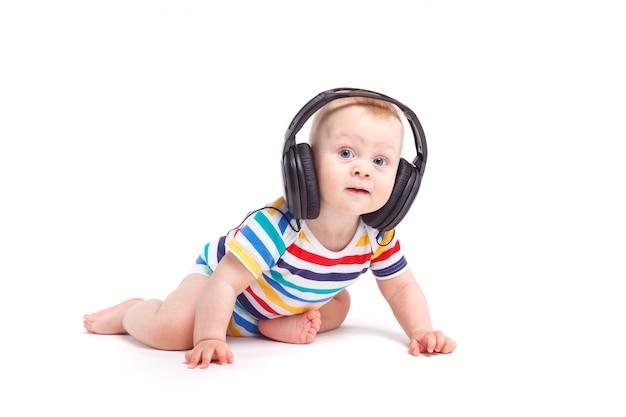 Leuke verbaasde kleine jongen in kleurrijk overhemd met hoofdtelefoons op hoofd
