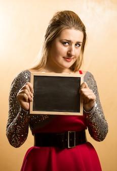 Leuke verlegen vrouw poseren met leeg schoolbord