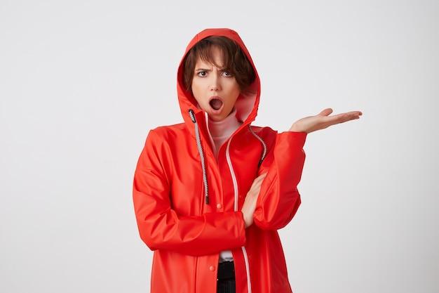 Leuke verontwaardigde jonge kortharige dame in rode regenjas, kijkt bewonderend met wijd open mond van verbazing. staand met gekruiste armen.