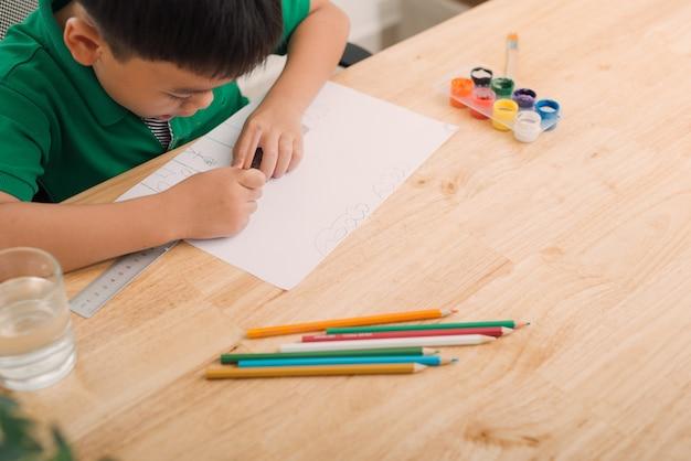 Leuke verwarde lachende jongen die huiswerk maakt, pagina's kleurt, schrijft en schildert. kinderen schilderen. kinderen tekenen. kleuter met boeken in de bibliotheek. kleurrijke potloden en papier op een bureau. creatieve jongen.